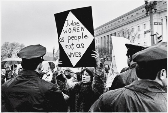 A young American woman holds up a sign as she protests for women